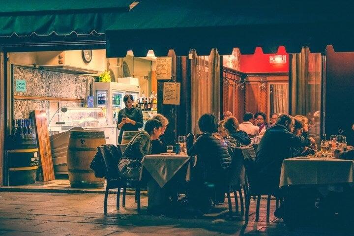 Terraza exterior de un bar en Venecia con gente sentada de noche