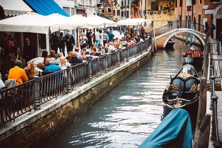 Bares en los canales de Venecia con gente sentada