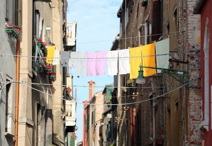 Calle de venecia con la ropa colgando entre los balcones