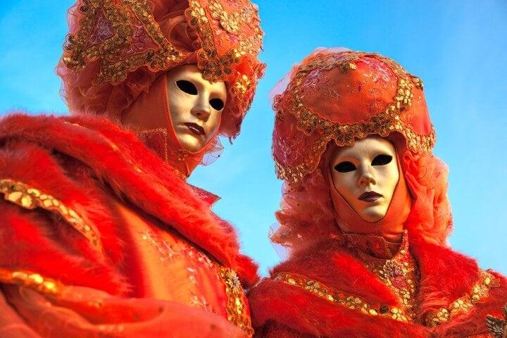 Dos personas disfrazadas con máscaras y trajes naranja en el carnaval de Venecia