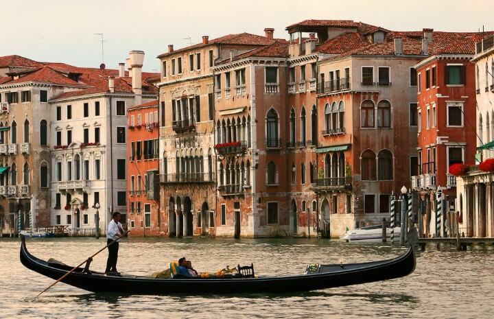 Canal veneciano con una góndola navegando