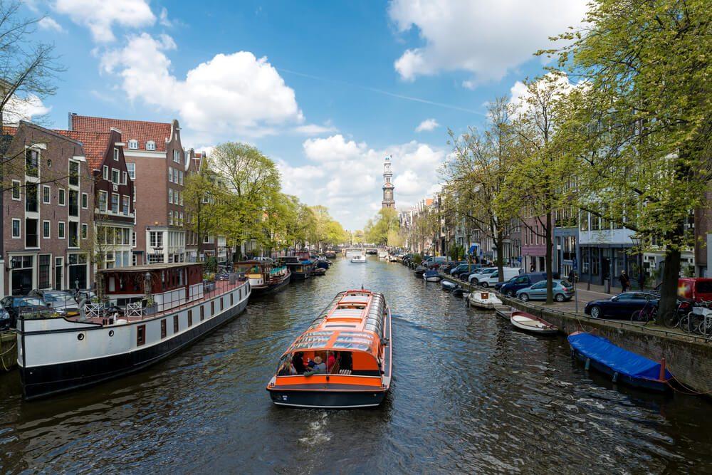 Barco turístico surca uno de los canales de Ámsterdam en los Países Bajos