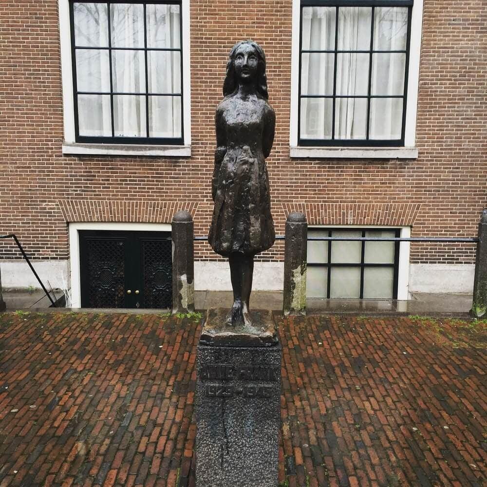 Estatua de Ana Frank delante de las ventanas de la  casa museo Annefrankhuis en Ámsterdam