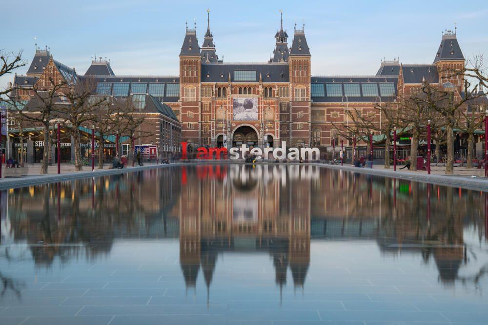 Fachada principal del Museo Nacional de Ámsterdam o Rijksmuseum con estanque y letras I amsterdam en frente