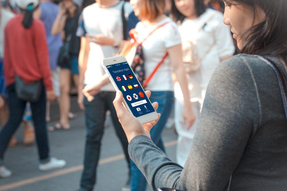 Una mujer consulta aplicaciones en su teléfono móvil en la calle