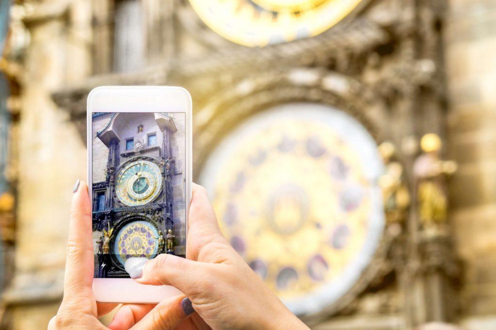 Un móvil saca una foto del reloj de Praga, en primer plano se ve el móvil, al fondo el reloj