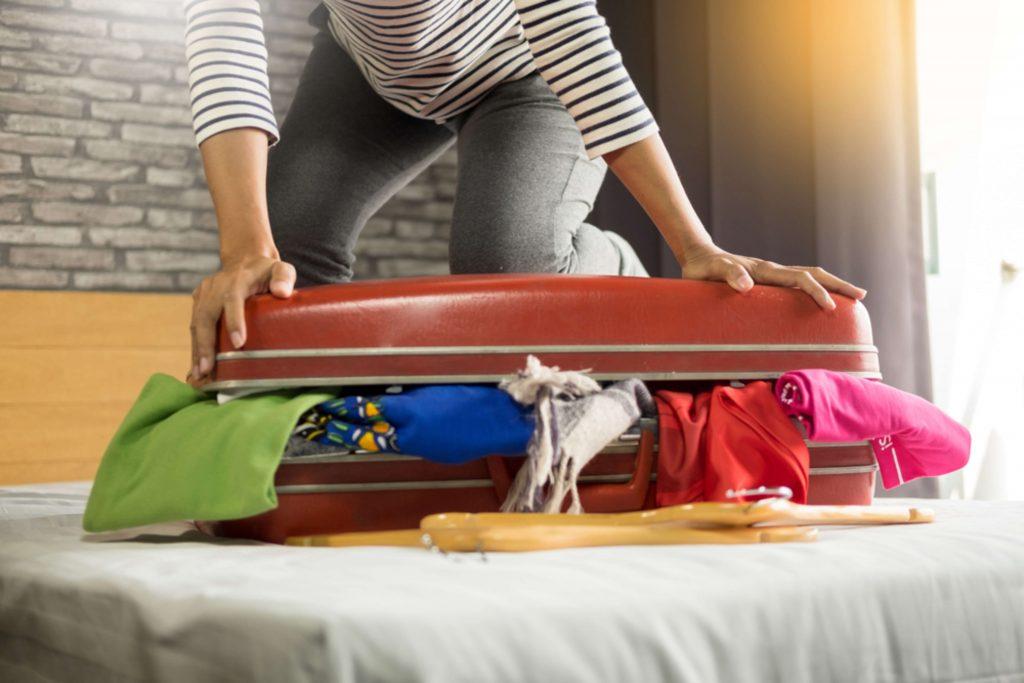 Una mujer intenta cerrar una maleta roja llena de ropa de colores
