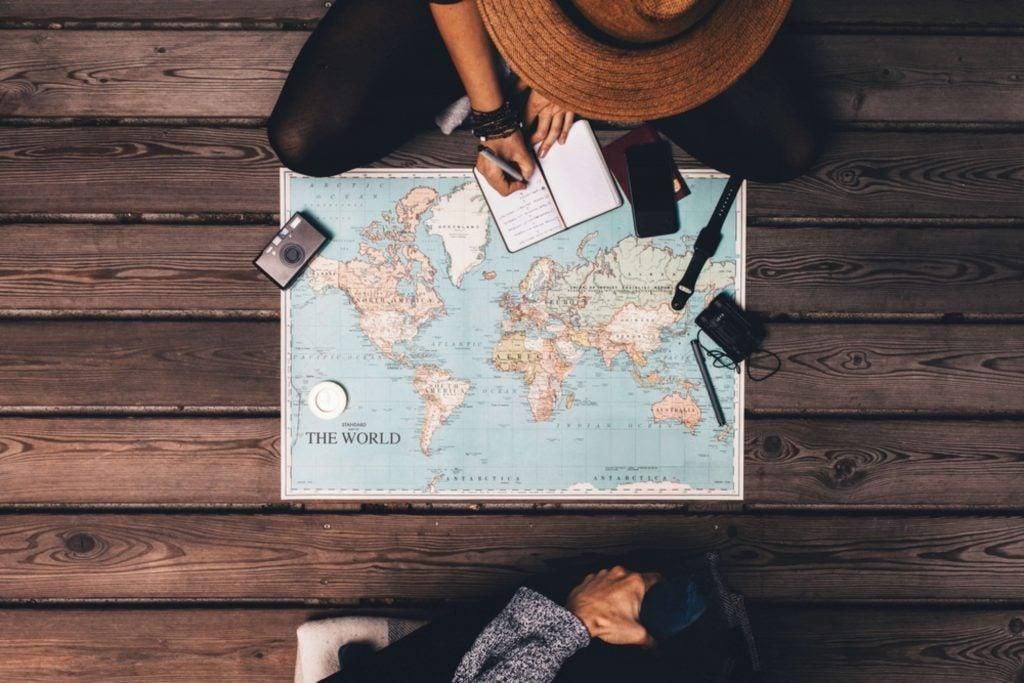 Chica con sombrero apunta en una libreta detalles de su viaje con un mapa a sus pies