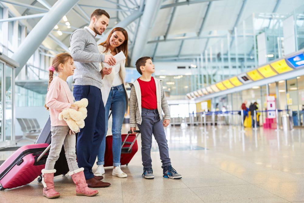 Una familia consulta sus billetes de avión en el aeropuerto antes de coger su vuelo e irse de vacaciones