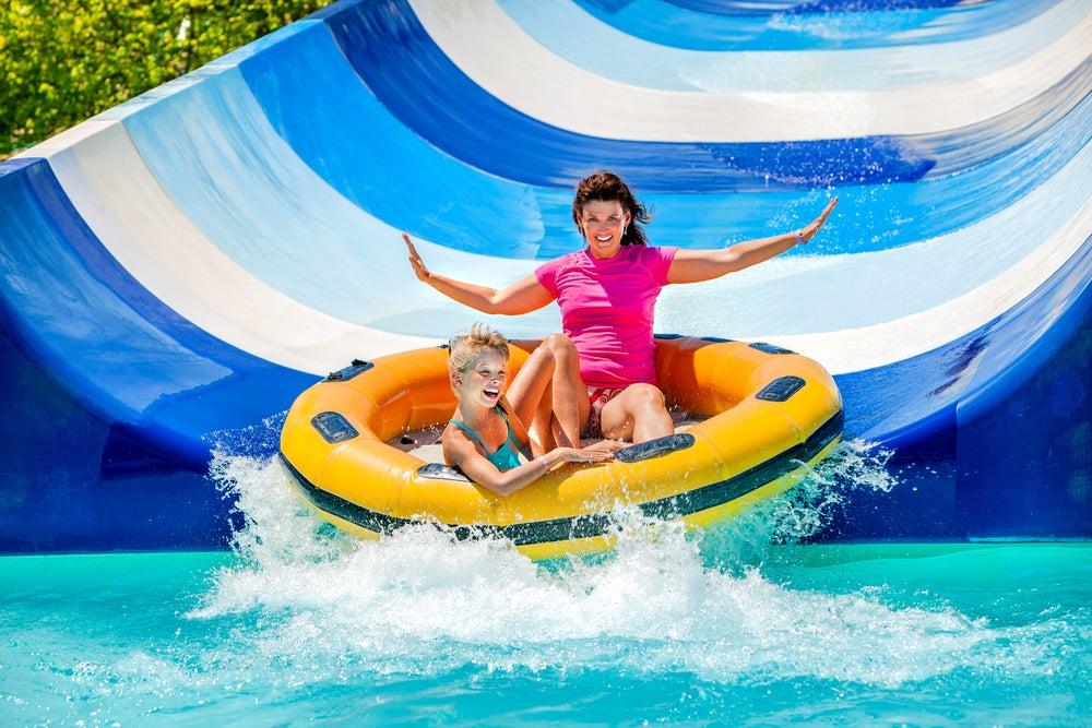 Madre e hija se deslizan por un tobogán en un parque aquático.