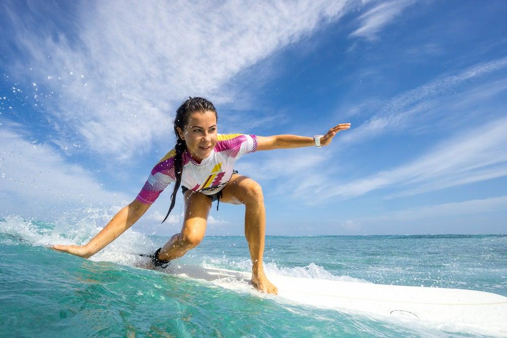 Mujer practicando surf en las costas de Benidorm.