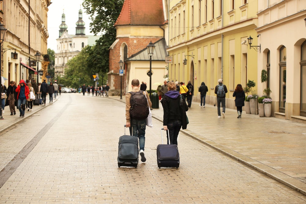 Dos turistas con maletas caminan por una de las calles del casco antiguo de Cracovia, Polonia.