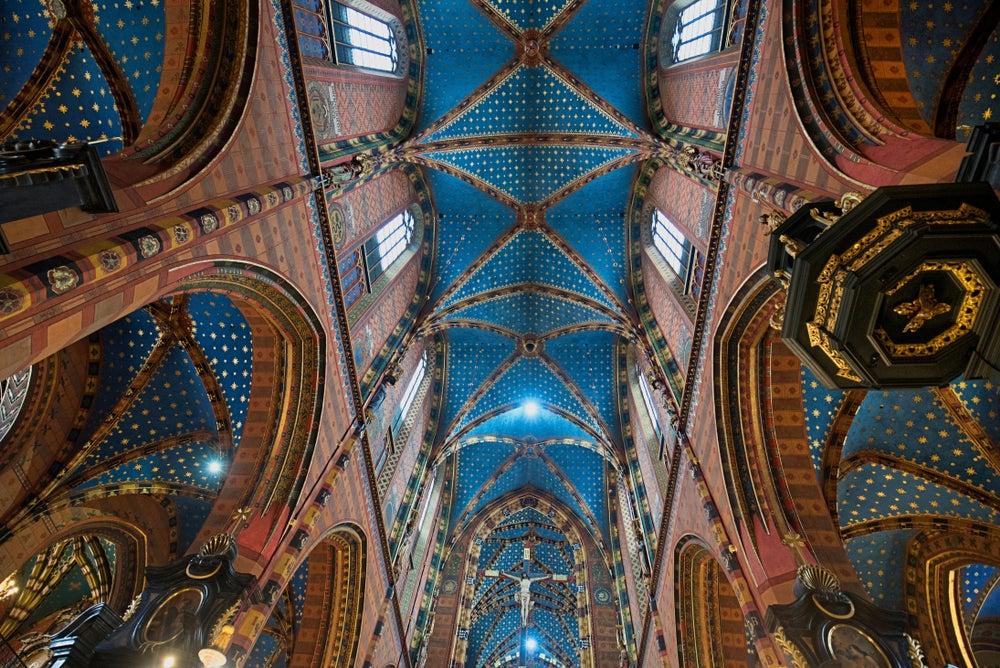 Interior de la Basílica de Santa María de Cracovia con sus arcos y columnas decorados con vivos colores.