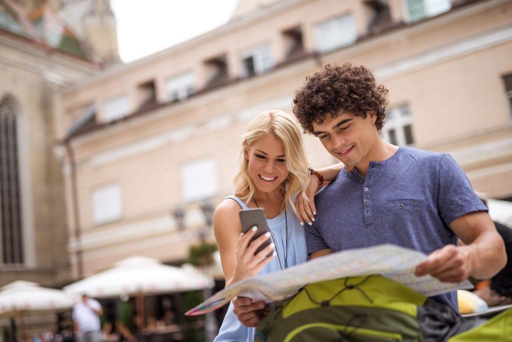 Pareja de jóvenes de viaje mirando al móvil y al mapa