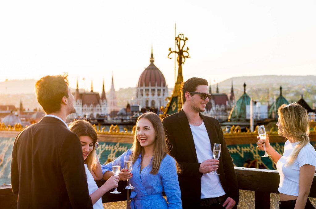 Jóvenes tomando un cóctel en una azotea de Budapest, con vistas al Parlamento húngaro