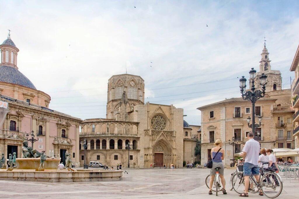 Turistas en bicicleta visitan la Plaza de la Virgen de València