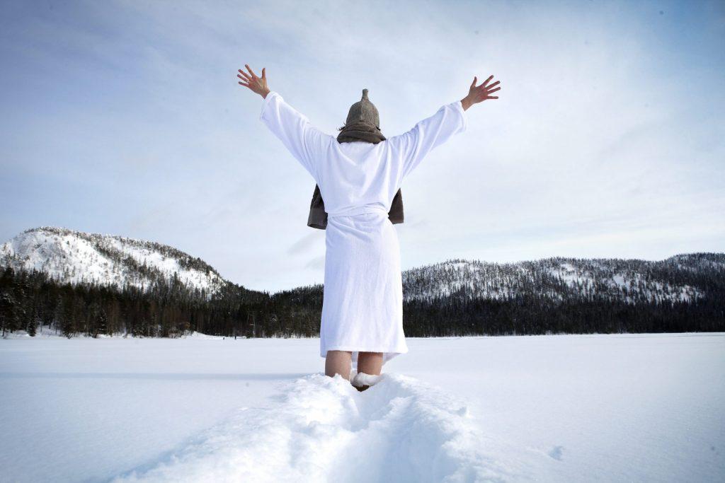 Mujer andando en albornoz por la nieve tras salir de la sauna en la Laponia finlandesa