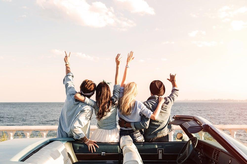 Vista posterior de jóvenes amigos felices parados con las manos levantadas cerca del coche