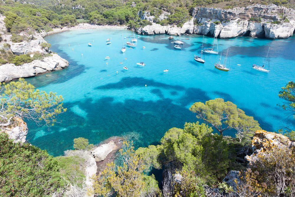 Vista aérea de la Cala Macarella con barcos y yates en Menorca