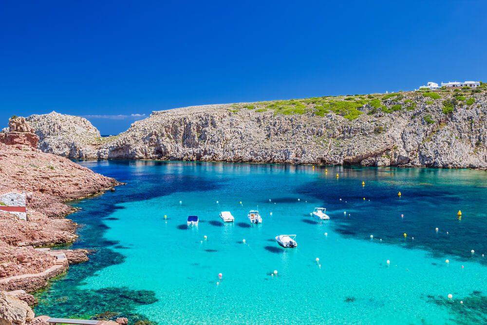 Cala Morell rodeada de acantilado rocoso en Menorca, Baleares