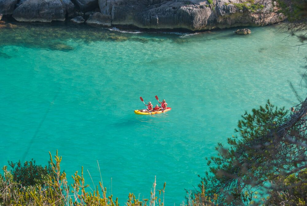 Dos personas practican Kayak en las aguas turquesas de Cala en Porter, Menorca
