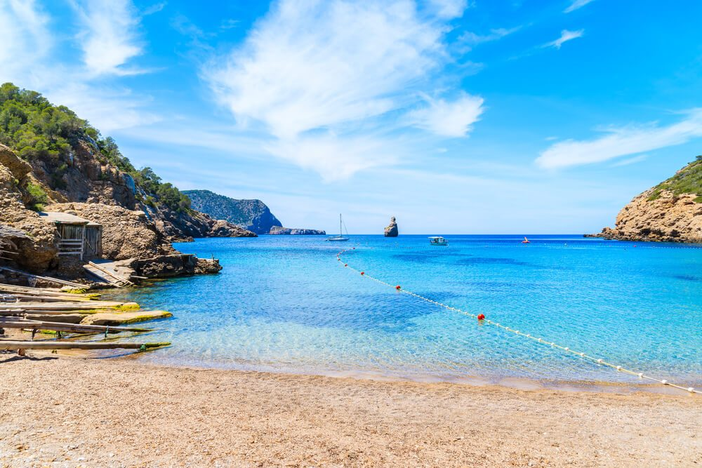 Arenal de la playa en Cala Benirràs con el islote Es Cap Bernat al fondo en Ibiza