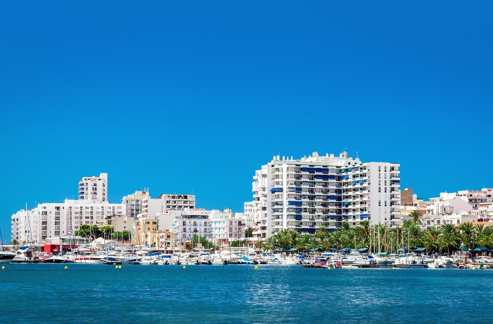 Vista del litoral de Sant Antoni de Portmany con muelle y edificios, en Ibiza