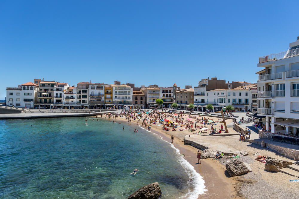 Playa central de L'Escala con bañistas y edificios del casco antiguo del pueblo, en Girona