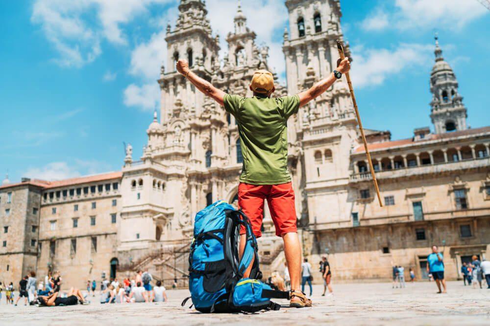 Peregrino con mochila en el suelo extiende los brazos para celebrar su llegada a la Catedral de Santiago de Compostela, final del Camino de Santiago