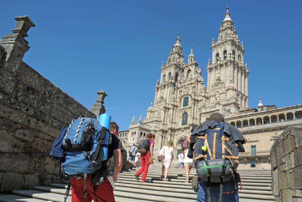 Peregrinos con mochila suben las escaleras antes de llegar a la meta del Camino, la Catedral de Santiago de Compostela