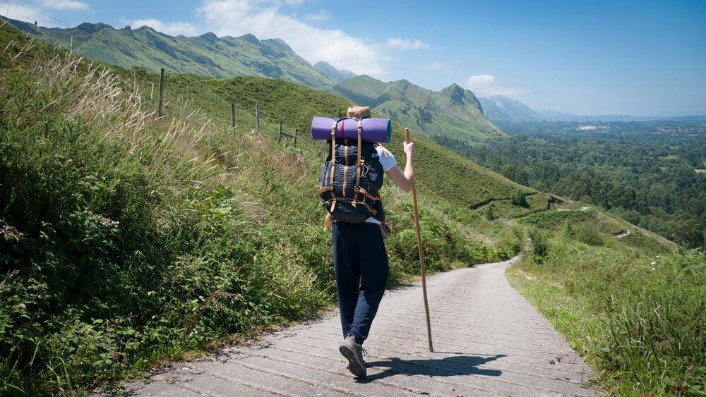 Peregrino con mochila y bastón recorre a pie el Camino de Santiago