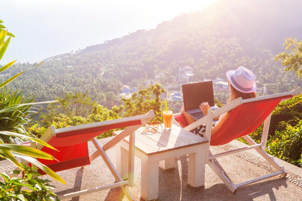 Chica teletrabaja en tumbona en su portátil con vistas a la montaña y zumo