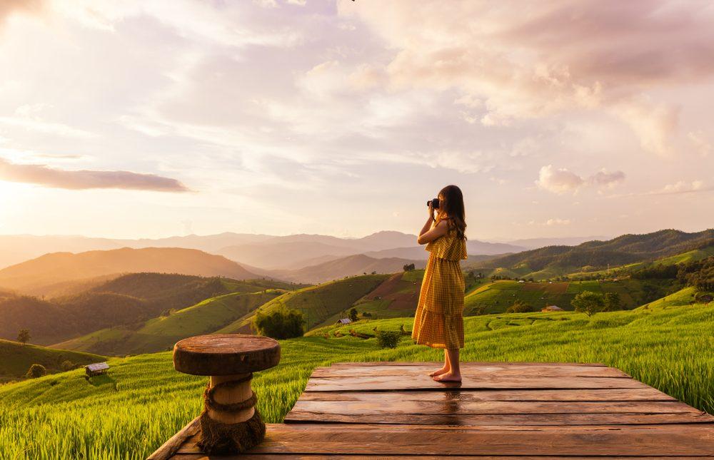 Mujer fotografiando los campos en Chiang Mai, Tailandia, donde trabajan a distancia