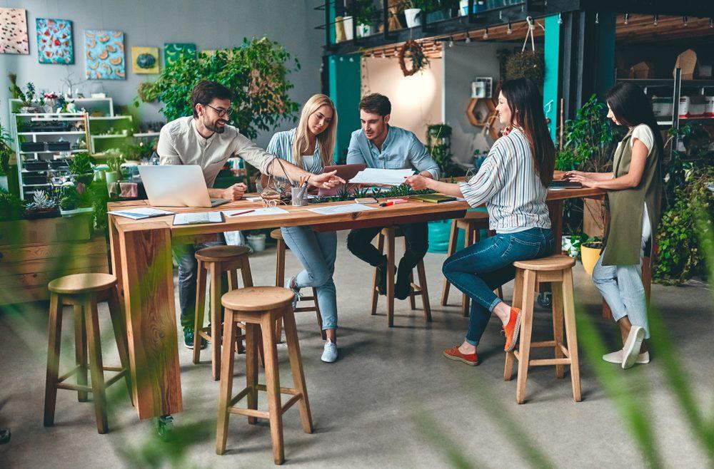 Espacio de coworking con mesa centrar y jóvenes reunidos con material de trabajo