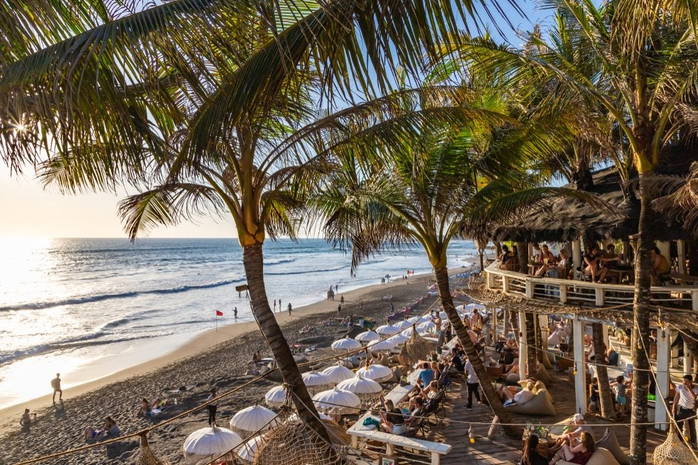 Playa de Bali, Indonesia, con palmeras y un restaurante a pie de playa lleno de gente