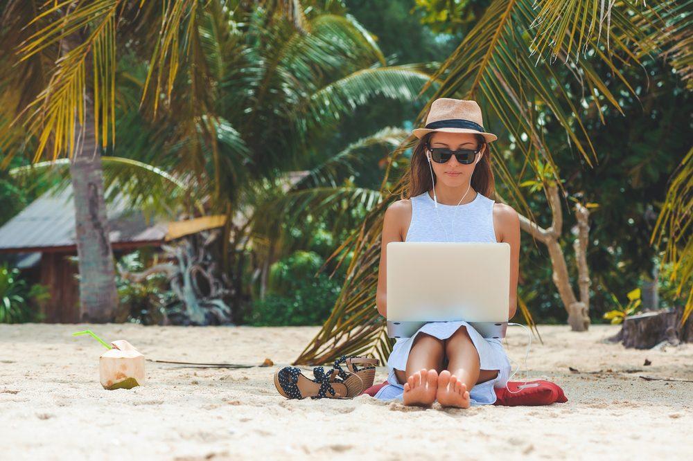 Chica trabaja en remoto en su ordenador portátil sentada en la arena de la playa, descalza, con sombrero, gafas de sol y bebida de coco
